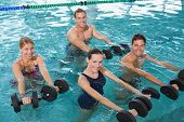 foto of day care center  - Happy fitness class doing aqua aerobics with foam dumbbells in swimming pool at the leisure centre - JPG