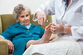 stock photo of chiropodist  - Nurse assists an elderly woman with chiropody and body care at home - JPG