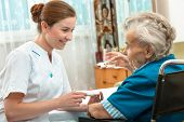stock photo of nursing  - female nurse giving senior woman medical pills - JPG