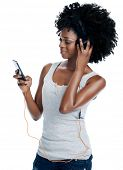 stock photo of afro  - African woman with afro with headphones on listening to music from her phone isolated - JPG