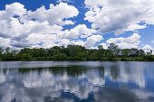 foto of puffy  - Beautiful summer landscape of a lake with puffy white cumulus clouds in the sky reflecting in the water - JPG