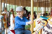 picture of carnival ride  - cheerful little boy enjoying his ride at carousel in amusement park - JPG