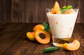 stock photo of apricot  - homemade yogurt with ripe apricots on wooden background - JPG
