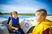 stock photo of life-boat  - Two kids sitting in the bow of a boat with there life jackets having fun - JPG