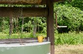 stock photo of pulley  - edge of old rustic well pulley with chain and mottled clay cup - JPG