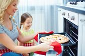 stock photo of take out pizza  - Portrait of happy young woman taking pizza out of oven - JPG