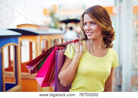 Female buyer with paperbags visiting department store