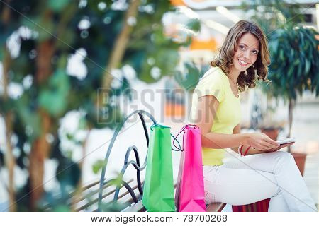Feminine buyer resting on bench in the mall after shopping