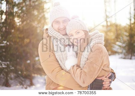 Young amorous couple embracing and looking at camera outdoors
