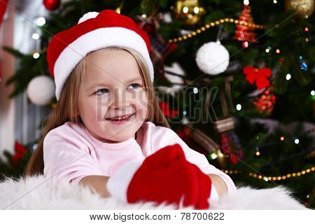 Little girl in Santa hat and mittens lying on fur carpet on Christmas tree background
