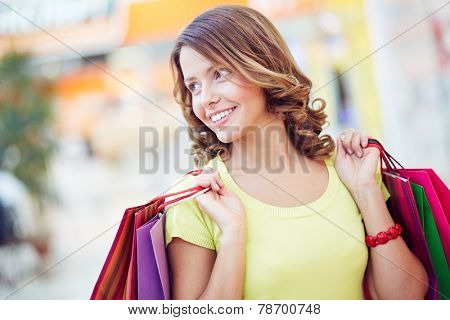 Young shopaholic with curly hair holding paper-bags