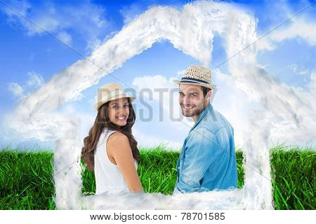 Happy hipster couple holding hands and smiling at camera against field of grass under blue sky