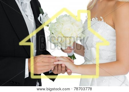 Young bridegroom putting on the wedding ring on his wifes finger against house outline