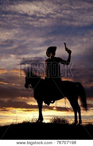 Silhouette Of Cowboy With Gun Sitting In Saddle On Horse