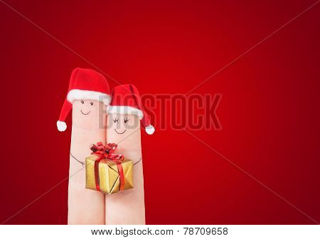Fingers Faces In Santa Hats With Gift Box On Dark Red Background. Celebrating Concept For Christmas