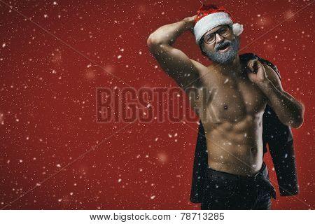 Cheerful Shirtless Santa On Snowy Red Backgrouund