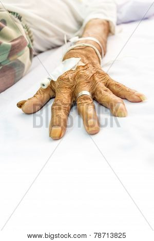 Old Patient's Hand With Plug On Bed In Hospital