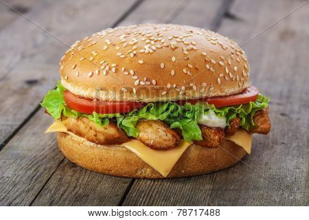 hamburger with chicken and cheese on a wooden surface