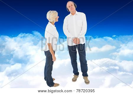 Annoyed woman being ignored by her partner against bright blue sky over clouds