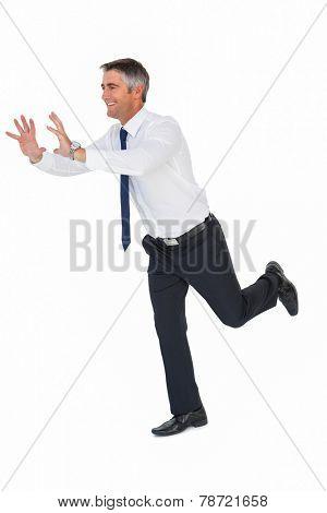 Happy businessman without jacket catching something on white background