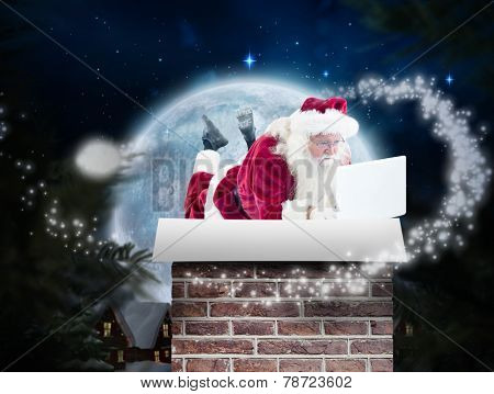 Santa lies in front of his laptop against christmas village under full moon