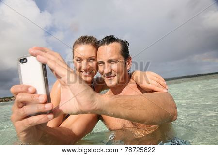Couple making selfie in the sea with waterproof smartphone