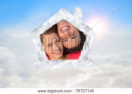 Close up of two friends looking upwards while lying head to shoulder against blue sky with white clouds
