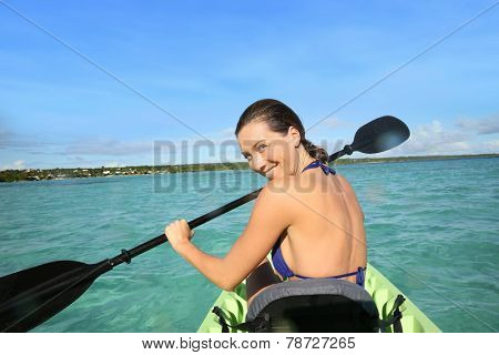 Back view of beautiful woman paddling in canoe