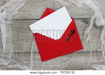 Blank white letter in red envelope with key on white cloth background