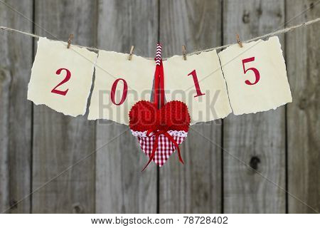 Year 2015 antique paper sign with red heart hanging on clothesline