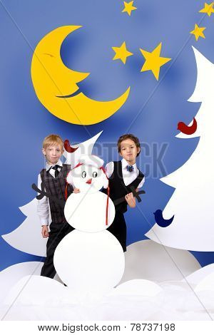 Cute girl and boy playing together in a cartoon fairy snowy forest. The magic of Christmas night. Full length portrait.