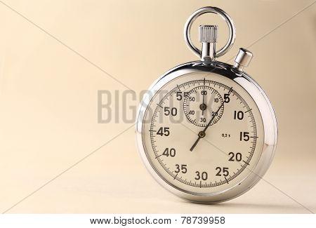 Stopwatch Closeup On Beige Background