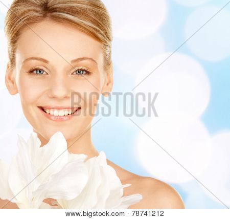 beauty, people and health concept - beautiful young woman with bare shoulders over blue lights background