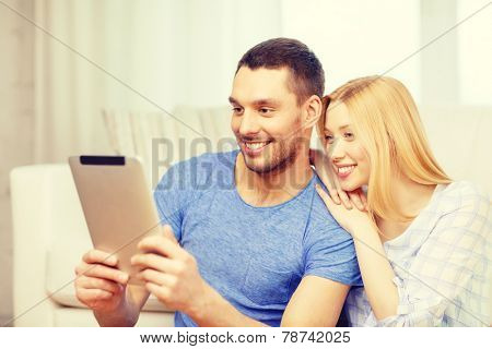 love, family, technology, internet and happiness concept - smiling happy couple witl tablet pc computer sitting on the floor at home