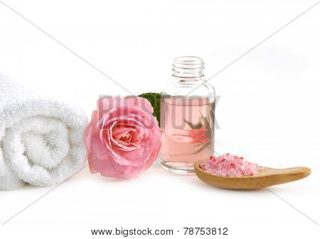 rose with massage oil ,salt in bowl ,spoon on white background