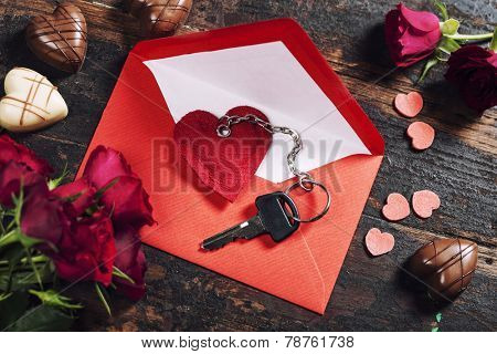 Red  envelop, roses, chocolate and key On old wood background