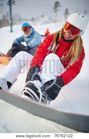 Smiling female snowboarder in activewear on winter resort