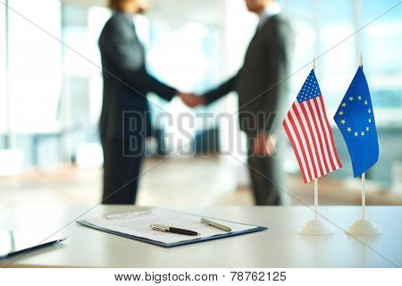 American flag, flag of European Union and business contract on background of two political leaders handshaking