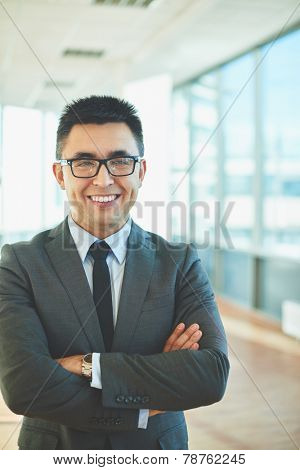 Happy employer with crossed arms looking at camera