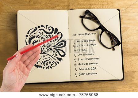 Hand holding red pencil against overhead of reading glasses with notebook
