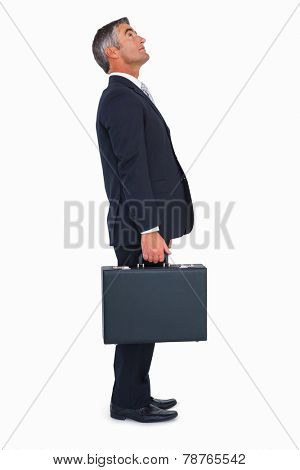 Businessman standing and holding briefcase on white background