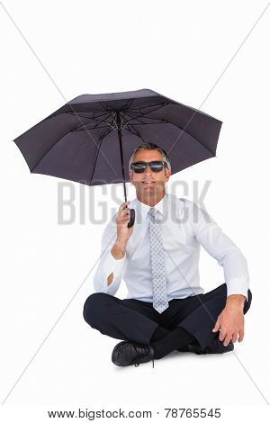Businessman wearing sunglasses and sheltering with umbrella on white background