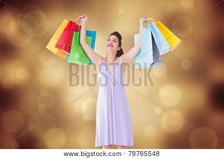 Smiling brunette showing shopping bags against orange abstract light spot design