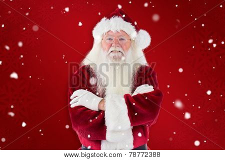 Santa smiles with folded arms against red snowflake background