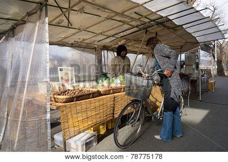 TAKAYAMA, JAPAN - DECEMBER 3, 2014: Local shopping at the Miyagawa morning market in Takayama, Japan. This morning market sells food items, groceries to farm produce and is common in rural Japan.