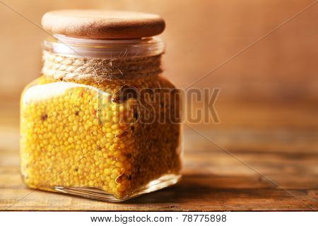 Dijon Mustard in glass jar on wooden background