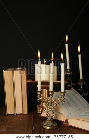 Retro candlesticks with candles and books, on wooden table, on black background