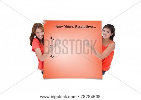 Teenage girls looking at the camera while pointing their fingers on a blank poster against orange card
