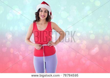 Festive athletic brunette measuring her waist against blue and pink light spot design