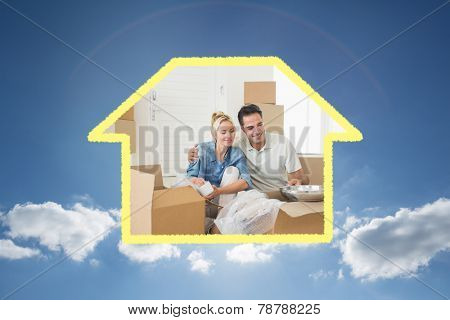 Smiling couple unpacking boxes in a new house against cloudy sky with sunshine